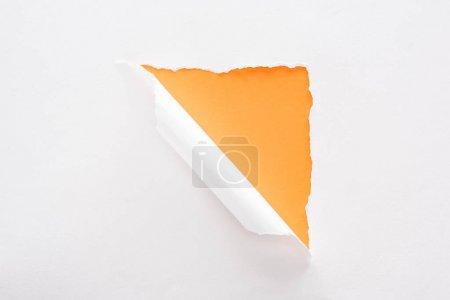 Foto de Papel blanco desgarrado y laminado sobre fondo naranja colorido - Imagen libre de derechos