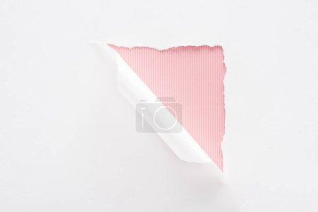 Foto de Papel blanco desgarrado y laminado sobre fondo colorido a rayas rosas - Imagen libre de derechos