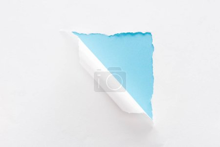 Foto de Papel blanco desgarrado y laminado sobre fondo azul colorido - Imagen libre de derechos