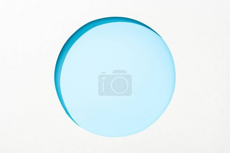 Photo for Cut out round hole in white paper on light blue colorful background - Royalty Free Image