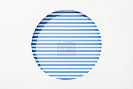 Photo pour Trou rond découpé dans le papier blanc sur le fond rayé bleu et blanc - image libre de droit
