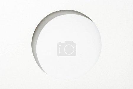 Foto de Agujero redondo cortado en papel blanco sobre fondo simple blanco - Imagen libre de derechos