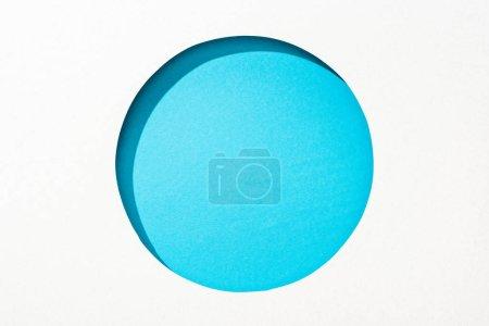Photo pour Trou rond découpé dans le papier blanc sur le fond bleu - image libre de droit