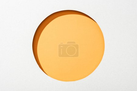 Photo for Cut out round hole in white paper on orange background - Royalty Free Image