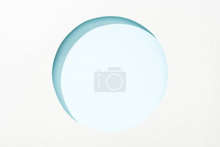Photo for Cut out round hole in white paper on light blue background - Royalty Free Image