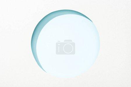 Photo pour Trou rond découpé dans le papier blanc sur le fond bleu clair - image libre de droit