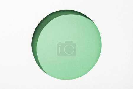 Photo for Cut out round hole in white paper on green background - Royalty Free Image