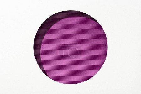 Photo pour Trou rond découpé dans le papier blanc sur le fond violet rayé - image libre de droit