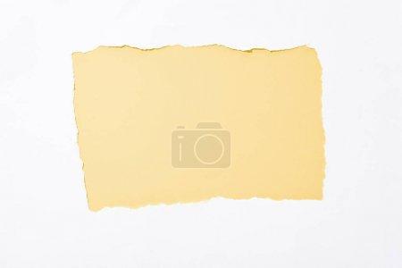 Photo pour Fond coloré jaune clair dans le trou déchiré blanc de papier - image libre de droit