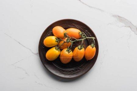 vista superior de tomates amarillos en placa de madera sobre superficie de mármol