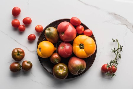 Photo for Top view of tomatoes on wooden plate near scattered tomatoes on marble surface - Royalty Free Image