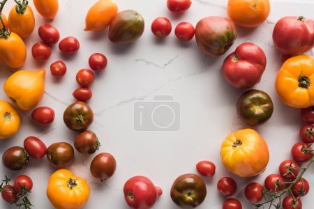 Photo for Top view of scattered tomatoes with empty space in middle on marble surface - Royalty Free Image