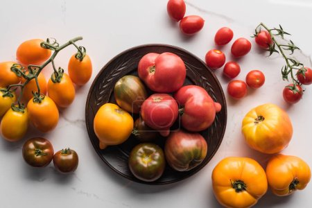 Photo for Top view of tomatoes on wooden plate near scattered tomatoes on white marble surface - Royalty Free Image