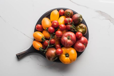 Foto de Top view of tomatoes on wooden pizza pan on marble surface - Imagen libre de derechos