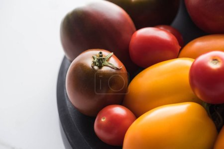 Photo for Close up view of red and yellow tomatoes on wooden pizza pan on marble surface - Royalty Free Image