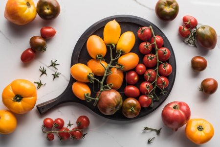 Photo for Top view of different yellow, red and cherry tomatoes on pizza pan on marble surface - Royalty Free Image
