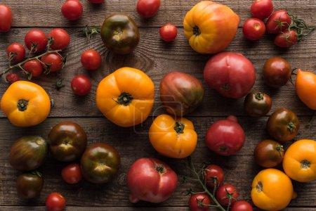 Photo pour Vue supérieure des tomates rouges et jaunes dispersées sur la table en bois - image libre de droit