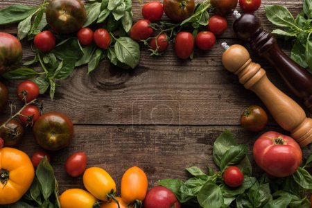 Photo for Top view of tomatoes, spinach, pepper mill, salt mill and empty space in middle on wooden table - Royalty Free Image