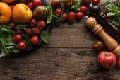 """Постер, картина, фотообои """"верхний вид мельницы перца и соляной мельницы возле помидоров и шпината на сковороде для пиццы на деревянной поверхности"""""""