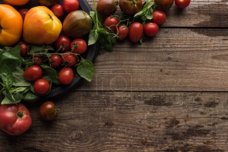 Photo for Top view of tomatoes and spinach on pizza pan on wooden table - Royalty Free Image