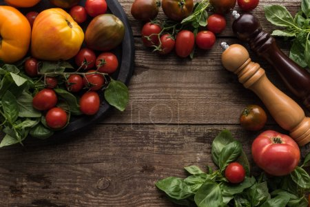 Photo for Top view of tomatoes and spinach on pizza pan  near pepper mill and salt mill on wooden surface - Royalty Free Image