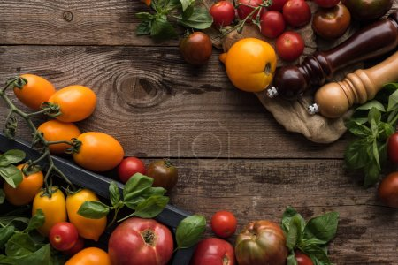 Photo for Top view of tomatoes and spinach in box near pepper mill and salt mill on piece of fabric on wooden surface - Royalty Free Image