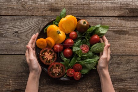 Photo for Cropped view of woman holding plate with spinach and sliced tomatoes on wooden table - Royalty Free Image