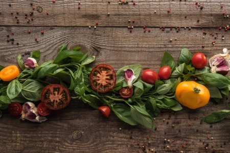 Photo for Flat lay with spinach, sliced tomatoes, garlic and scattered pepper on wooden table - Royalty Free Image