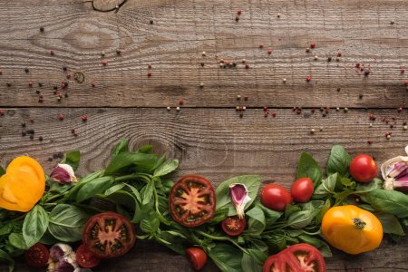 Photo for Top view of spinach, sliced tomatoes, garlic and scattered pepper on wooden table - Royalty Free Image