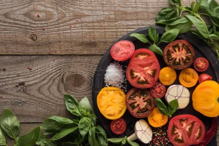 Photo for Top view of tomatoes, garlic, chilli pepper, salt and pepper on pizza pan near spinach on wooden table - Royalty Free Image