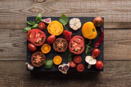 Foto de Vista superior de tomates, ajo, espinacas, chile en la bandeja en la mesa de madera - Imagen libre de derechos