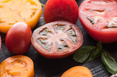 """Постер, картина, фотообои """"close up view of sliced red and yellow tomatoes on black wooden tray """""""