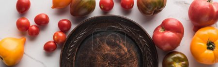 Photo for Panoramic shot of empty wooden plate near scattered tomatoes on white marble surface - Royalty Free Image