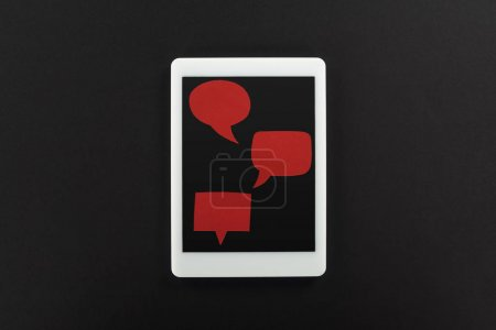 top view of digital tablet with empty red speech bubbles on black background, cyberbullying concept