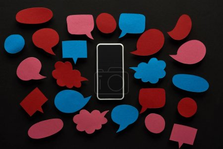 Photo for Top view of smartphone with blank screen on black background with empty red and blue speech bubbles, cyberbullying concept - Royalty Free Image