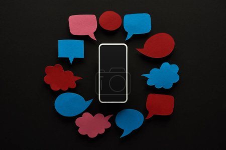 top view of smartphone on black background with empty speech bubbles, cyberbullying concept