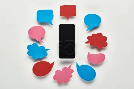 Photo pour Vue du haut du smartphone avec écran blanc sur fond blanc près de bulles d'expression colorées vides, concept de cyberintimidation - image libre de droit
