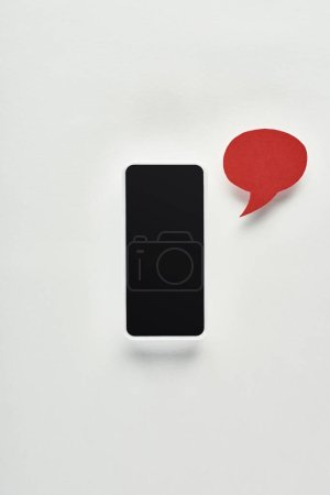 Photo for Top view of smartphone with blank screen on white background near red empty speech bubble, cyberbullying concept - Royalty Free Image