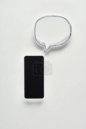 Photo pour Vue supérieure du smartphone avec l'écran blanc sur le fond blanc près de la bulle vide de discours, concept de cyberintimidation - image libre de droit