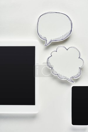 Photo for Top view of digital tablet and smartphone on white background near empty speech bubbles, cyberbullying concept - Royalty Free Image