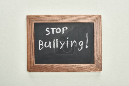 Photo for Top view of chalkboard in wooden frame with stop bullying lettering on grey background - Royalty Free Image
