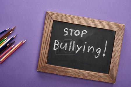 Foto de Vista superior de la pizarra en marco de madera con stop bullying letras cerca de lápices de colores sobre fondo púrpura - Imagen libre de derechos