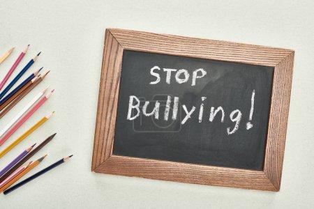 Foto de Vista superior de la pizarra en marco de madera con stop bullying letras cerca de lápices de colores sobre fondo gris - Imagen libre de derechos