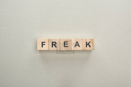 top view of wooden blocks with freak lettering on grey background, bullying concept