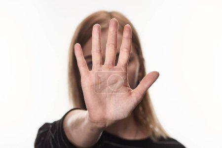 Photo pour Foyer sélectif de la victime féminine de l'intimidation montrant le signe d'arrêt isolé sur le blanc - image libre de droit
