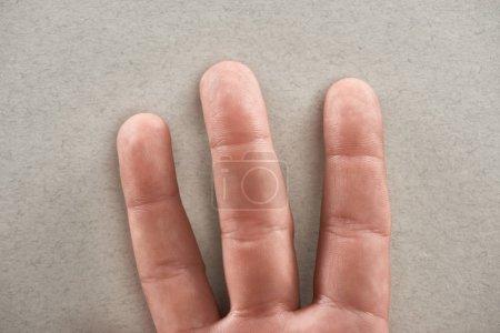 Photo pour Vue partielle de l'homme montrant trois doigts sur fond gris - image libre de droit