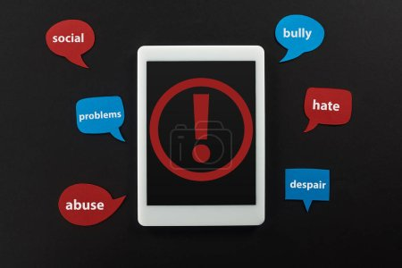 top view of digital tablet with exclamation mark on screen on black background near speech bubbles with cyberbullying words