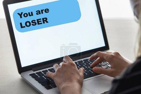 Photo pour Vue recadrée de fille tapant sur le clavier d'ordinateur portable avec vous sont le message perdant à l'écran, concept de cyberintimidation - image libre de droit