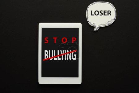 Photo pour Vue supérieure de la tablette numérique avec l'arrêt de l'intimidation lettrage sur l'écran sur le fond noir près de bulle de parole blanche avec le mot perdant - image libre de droit