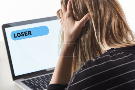Photo for Offended blonde girl as victim of cyberbullying sitting near laptop with loser message on screen - Royalty Free Image